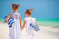 Adorable little girls with towels at tropical beach. Cute little girls at beach with towels Stock Photography