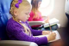 Adorable little girls traveling by an airplane. Child sitting by aircraft window and drawing a picture with colorful pencils. Traveling abroad with kids royalty free stock image