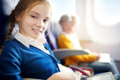 Adorable little girls traveling by an airplane. Child sitting by aircraft window and drawing a picture with colorful pencils. Stock Image