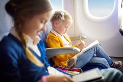 Adorable little girls traveling by an airplane. Child sitting by aircraft window and drawing a picture with colorful pencils. Trav Stock Image