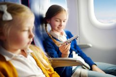 Adorable little girls traveling by an airplane. Children sitting by aircraft window and playing with toy plane. Traveling with kid. Adorable little girls stock images
