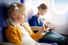 Adorable little girls traveling by an airplane. Children sitting by aircraft window and playing with toy plane. Traveling with kid Royalty Free Stock Photography