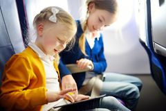 Adorable little girls traveling by an airplane. Children sitting by aircraft window and using a digital tablet during the flight. Royalty Free Stock Image