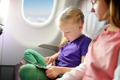 Adorable little girls traveling by an airplane. Children sitting by aircraft window and using a digital tablet during the flight. Traveling abroad with kids stock photography