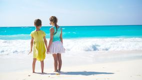 Adorable little girls walking on the beach. Back view of kids together enjoy sea view. Adorable little sisters at beach during summer vacation stock video footage