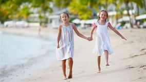 Adorable little girls walking on the beach and having fun together. On Caribbean beach stock footage