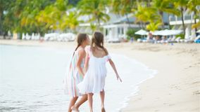 Adorable little girls walking on the beach and having fun together. Adorable little sisters at beach during summer vacation stock video