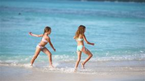 Adorable little girls walking on the beach and having fun together. Adorable little girls at beach during summer vacation having fun and running on the seashore stock footage