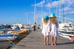 Adorable little girls walking in a port on summer Stock Photography