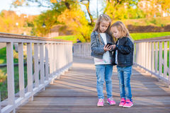 Adorable little girls at warm autumn day outdoors Stock Photo