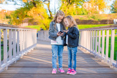 Adorable little girls at warm autumn day outdoors Royalty Free Stock Photo