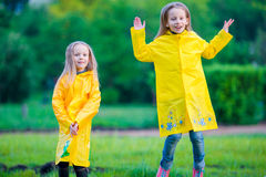 Adorable little girls wearing waterproof coat have fun outdoors Royalty Free Stock Photo