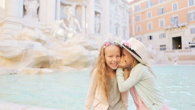 Adorable little girls whispering sitting on the edge of Fountain of Trevi in Rome. Happy kids enjoy their european stock video