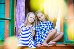 Adorable little girls in the window of rural house Royalty Free Stock Photo
