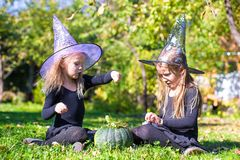 Adorable little girls in witch costume casting a Stock Photos