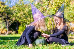 Adorable little girls in witch costume casting a Stock Photography