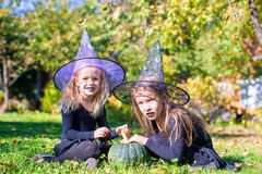 Adorable little girls in witch costume casting a Stock Images