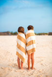 Adorable little girls wrapped in towel at tropical beach. Cute little girls at beach covered with towel Stock Images