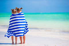 Adorable little girls wrapped in towel at tropical beach. Cute little girls at beach covered with towel Stock Photo