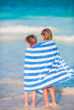 Adorable little girls wrapped in towel at tropical beach. Cute little girls at beach covered with towel Stock Photography