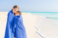 Adorable little girls wrapped in towel at tropical beach after swimming in the sea. Cute little girls at beach covered with towel Royalty Free Stock Photos