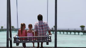 Adorable little girls and young father on swing stock footage