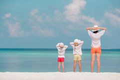 Adorable little girls and young mother on tropical white beach royalty free stock image