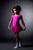 Adorable little gymnast posing in pink dress Stock Photo