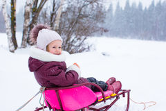 Adorable little happy girl sledding in winter Stock Image