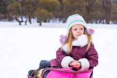 Adorable little happy girl sledding in winter Royalty Free Stock Photos