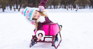 Adorable little happy girl sledding in winter Royalty Free Stock Photo