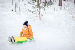 Adorable little happy girl sledding in winter snowy day. royalty free stock photography