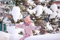 Adorable little happy girl sledding in winter snowy day. stock image