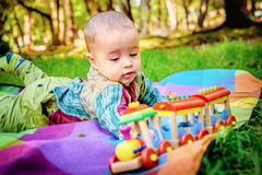 Adorable little infant boy laying on ground in the park and pal. Adorable little infant boy laying on ground in the park and playing with a wooden train Royalty Free Stock Image