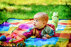 Adorable little infant boy laying on ground in the park and pal Royalty Free Stock Image