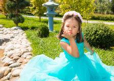 Adorable little kazakh, asian child girl on summer green nature background. royalty free stock photo