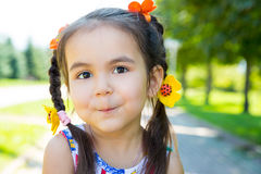 Adorable little kazakh, asian child girl on summer green nature background. Royalty Free Stock Photos
