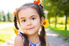 Adorable little kazakh, asian child girl on summer green nature background. Stock Photo