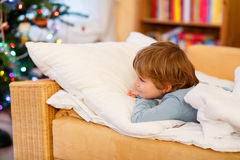 Adorable little kid boy with blond hairs looking on Christmas tr Stock Images