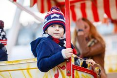 Little kid boy on ferris wheel on christmas market. Adorable little kid boy on a carousel, ferris wheel at Christmas funfair or market. Mother and sibling on Royalty Free Stock Image