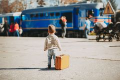 Adorable little kid boy dressed in red sweater on a railway station. Near train with retro old brown suitcase. Ready for vacation. Young traveler on the royalty free stock photography