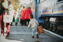 Adorable little kid boy dressed in red sweater on a railway station royalty free stock image