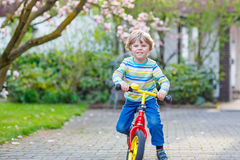Adorable little kid boy driving his first bike or laufrad Stock Photo