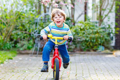 Adorable little kid boy driving his first bike or laufrad Royalty Free Stock Images