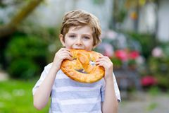 Adorable little kid boy eating huge big bavarian german pretzel. Happy blond child enjoying tasteful tratditional bread. Healthy food for happy kids Royalty Free Stock Photos