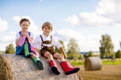 Adorable little kid boy and girl in traditional Bavarian costumes in wheat field on hay stack. Two little kid boy and girl in traditional Bavarian costumes in Royalty Free Stock Photos