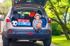 Little kid boy sitting in car trunk just before leaving for vaca. Adorable little kid boy sitting in car trunk just before leaving for summer vacation with his Royalty Free Stock Photos