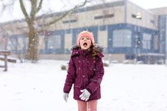 Adorable little kid girl in colorful clothes playing outdoors during snowfall. Active leisure with children in winter on cold snowy days. Happy child on winter Royalty Free Stock Photos
