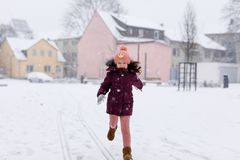 Adorable little kid girl in colorful clothes playing outdoors during snowfall. Active leisure with children in winter on cold snowy days. Happy child on winter Stock Photography