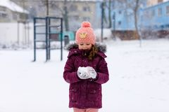 Adorable little kid girl in colorful clothes playing outdoors during snowfall. Active leisure with children in winter on cold snowy days. Happy child on winter Royalty Free Stock Photo